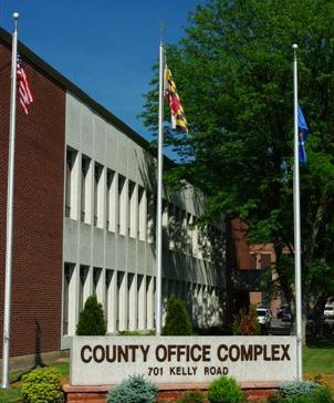 "A large brick and white building with a sign in front reading, ""County Office Complex, 701 Kelly"